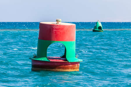 Two-color floating navigation buoy on the blue sea. Green buoy in the background. Selective focus.