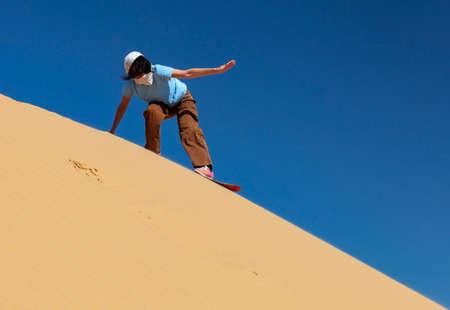 Sandboarding in the desert. A girl glides along a sand dune on a board. Imagens