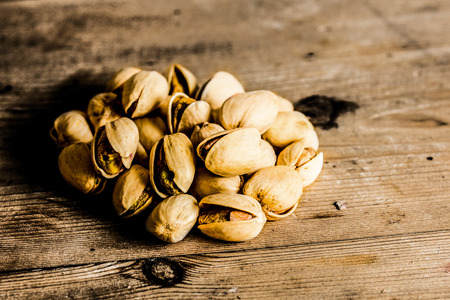 Group of pistachios on a rustic wooden background