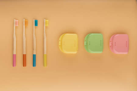 Wooden toothbrushes on colored background and transparent aligners, invisible orthodontics Banco de Imagens