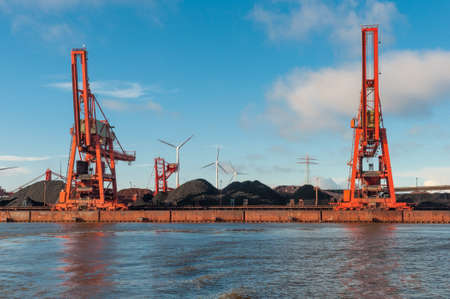 Cranes and piles of coals in port of Hamburg in germany Stock Photo