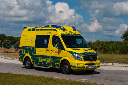 Vordingborg Denmark - June 26. 2016: Danish Falck Ambulance driving on the road on a sunny summer day