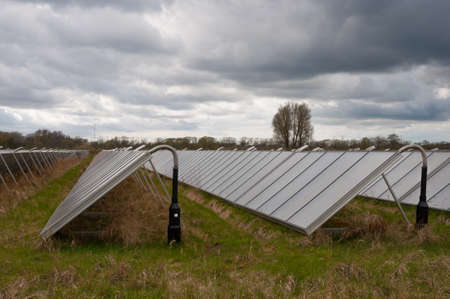Solar Panels on a field near a power plant in Denmark Stock Photo