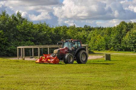 Aalborg Denmark - August 30. 2010: Tractor cutting grass in a park