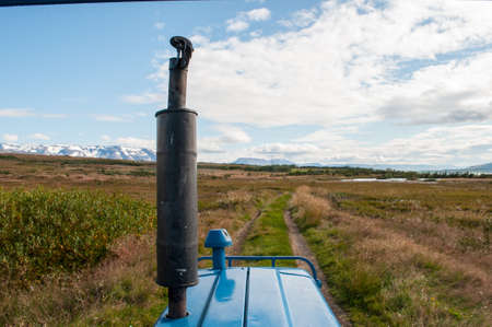 Blue tractor on a track in the Icelandic Countryside
