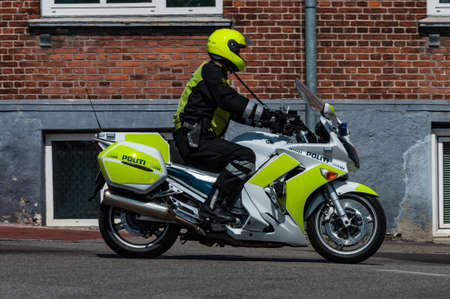 Vordingborg Denmark - May 28. 2016: Danish motorcycle Police officer driving in front of a house Editorial