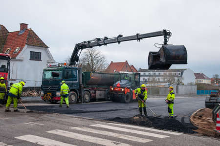 Vordingborg Denmark - January 19. 2018: Tarmac tipper with a crane doing some tarmac work