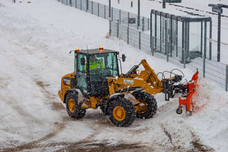 Vordingborg Denmark - February 3. 2018: Caterpillar wheel loader with a snowplow plowing snow during a blizzard Editorial