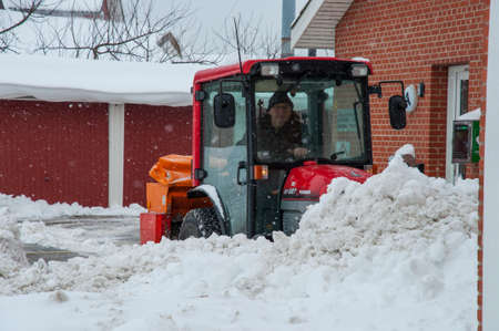 Vordingborg Denmark - February 3. 2018: Worker on a tractor plowing snow after a Blizzard