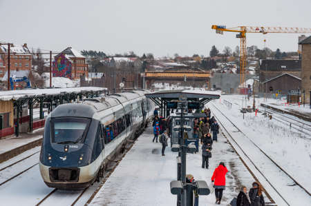 Naestved Denmark - March 1. 2018: Train at the platform at Naestved train station in Denmark with people waiting for another train Editorial