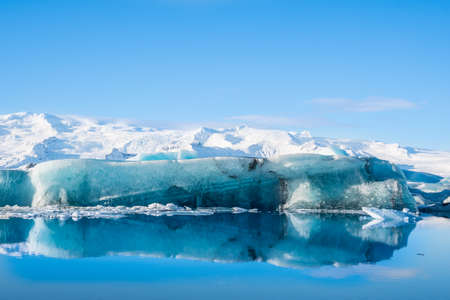 Icebergs in Jokulsarlon Glacier Lagoon in south Iceland with Vatnajokull glacier in the background Stock Photo - 131320874