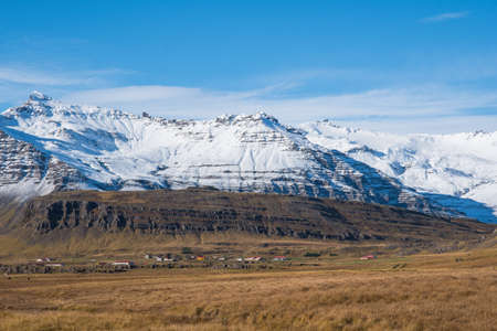 Icelandic countryside landscape with farms, mountains and Vatnajokull glacier on a sunny winter day Stock Photo
