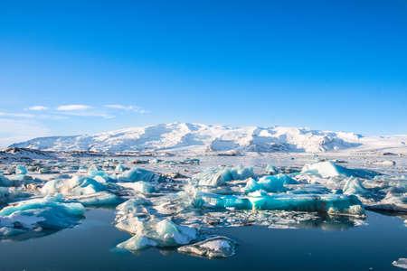 Icebergs in Jokulsarlon Glacier Lagoon in south Iceland with Vatnajokull glacier in the background Stock Photo - 131321355