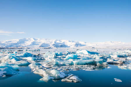 Icebergs in Jokulsarlon Glacier Lagoon in south Iceland with Vatnajokull glacier in the background Stock Photo - 131321453