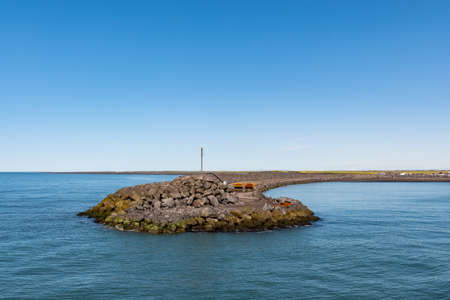 breakwater barrier in port of Landeyjahofn in South Iceland on a sunny summer day