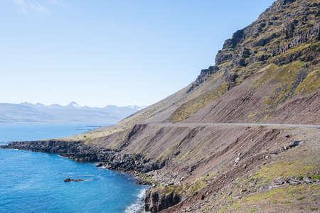 Road through Kambanesskridur land slides in east Iceland on a sunny summer day