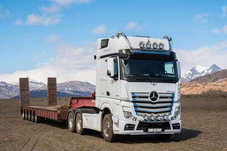 Hornafjordur Iceland - May 2. 2019: Mercedes Benz Actros Lorry with a machinery trailer in the Icelandic countryside