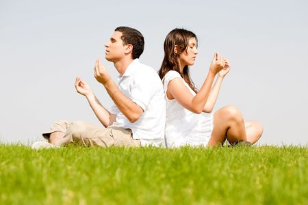 young couple sitting on grass and doing meditating Stock Photo - 5900164