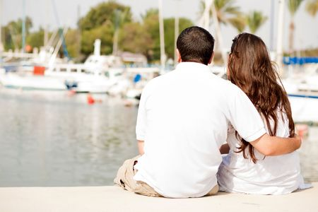 Rear View Of A Young Couple Seated On A Footbridge, Harbour View Stock Photo - 5900224
