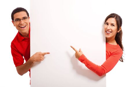 bill board: Happy young couple pointing at bill board Stock Photo
