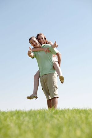 Happy Young Man Piggybacking His Girlfriend photo