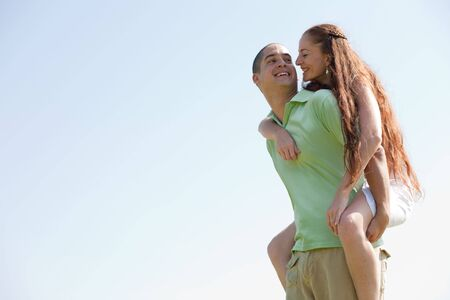 Happy Young Man Piggybacking His Girlfriend and smile photo