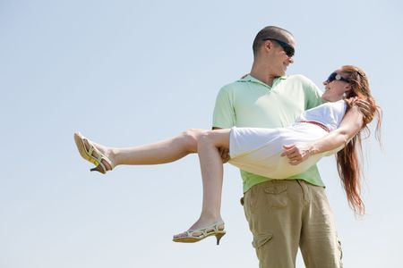 Young Guy Carrying His Girlfriend In His Arms, Outdoor photo