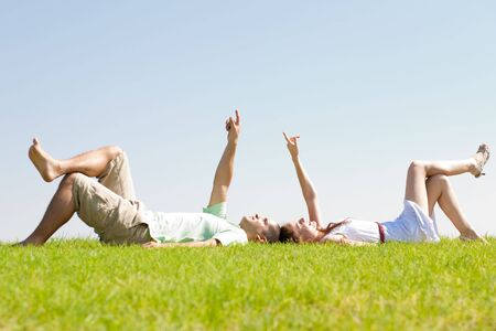 young couple lie down on grass and point to the sky, outdoor at park photo