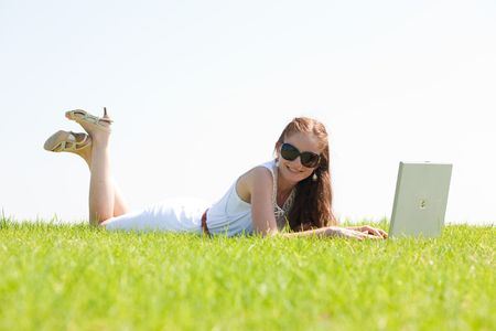 A cute young female lying on the grass in the park using a laptop photo