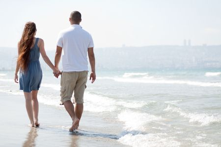 happy young couple walk at the beach photo