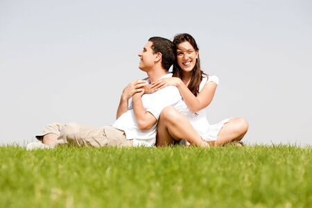Happy young women with arms around her husband in a green field photo