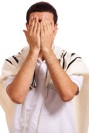 Portrait of jewish man closing face with his hands while praying on a white isolated background photo