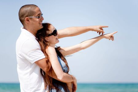 Romantic Couple holding each other and pointing at the sea photo
