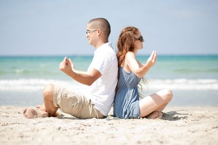 An attractive couple Meditating at the beach photo