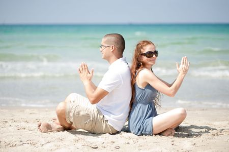 Couple sitting on the beach sand and doing exercises  photo