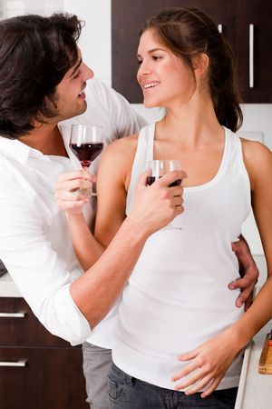 happy young couple enjoying their wine in kitchen photo