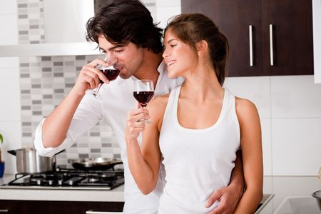 happy young couple drinking wine in kitchen