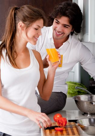 tomato juice: happy young couple in the kitchen and drink orange juice Stock Photo
