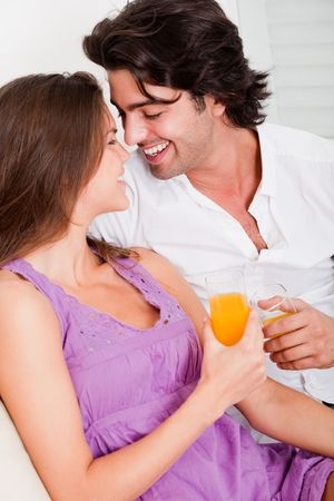 togther: Romantic couple having drink in their sofa