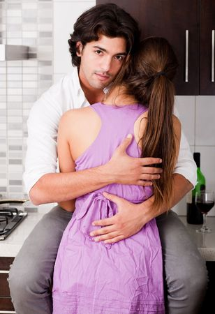 portrait of romantic young couple hug in the kitchen photo