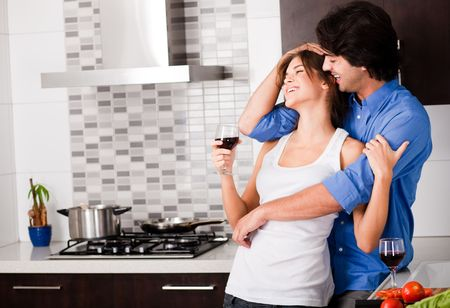 young couple hug in their kitchen Stock Photo