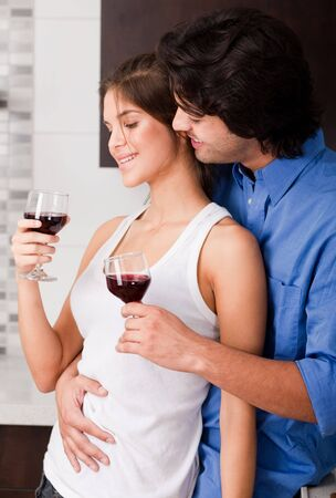 young couple toasting at kitchen photo