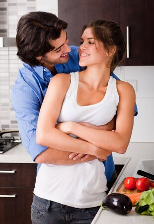 husband hold is wife in the kitchen and about to kiss  photo
