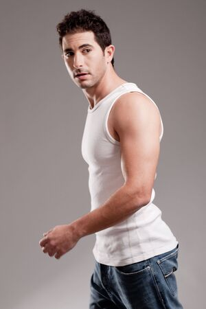 male muscles muscular pecs pectoral sexy young: Portrait of a  Handsome man looking left side on a isolated grey background Stock Photo