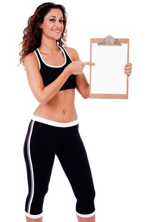Fitness woman showing a blank clip board on a isolated white background photo