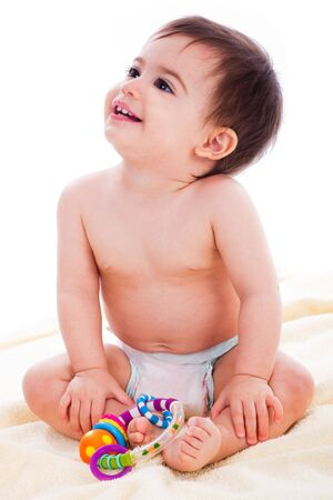hand towel: Baby sitting with toys and looking up in a white background