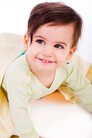 combed: Cute baby with combed hair under the yellow blanket in a white background