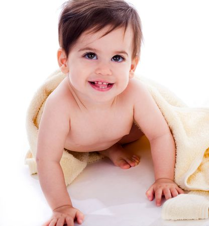 Baby showing its teeth under yellow towel in isolated background photo