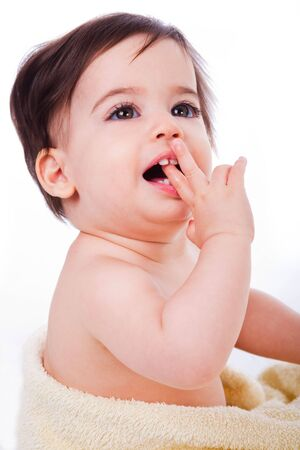 Baby with finger in mouth looking up in isolated background photo