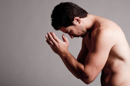 male muscles muscular pecs pectoral sexy young: Shirtless man praying in the grey isolated background Stock Photo